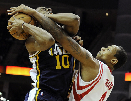 Houston Rockets' Greg Smith (4) knocks the ball away from Utah Jazz's Alec Burks (10) in the second half of an NBA basketball game Saturday, Dec. 1, 2012, in Houston. The Rockets won 124-116. (AP Photo/Pat Sullivan)
