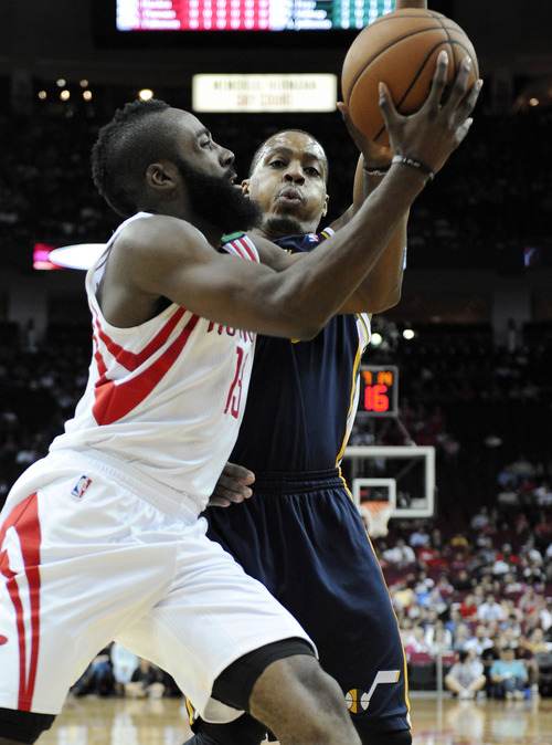 Houston Rockets' James Harden (13) goes to the basket in front of Utah Jazz's Randy Foye in the first half of an NBA basketball game on Saturday, Dec. 1, 2012, in Houston. (AP Photo/Pat Sullivan)