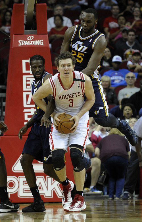 Houston Rockets' Omer Asik (3) looks to pass off the ball under pressure from Utah Jazz's DeMarre Carroll, left, and Al Jefferson (25) in the second half of an NBA basketball game on Saturday, Dec. 1, 2012, in Houston. The Rockets won 124-116. (AP Photo/Pat Sullivan)