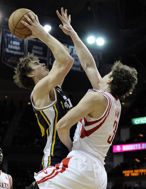 Houston Rockets' Omer Asik (3) is fouled by Utah Jazz's Gordon Hayward who goes to the basket in the second half of an NBA basketball game on Saturday, Dec. 1, 2012, in Houston. The Rockets won 124-116. (AP Photo/Pat Sullivan)
