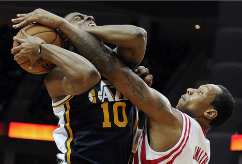 Houston Rockets' Greg Smith, right, knocks the ball away from Utah Jazz's Alec Burks (10) in the second half of an NBA basketball game on Saturday, Dec. 1, 2012, in Houston. The Rockets won 124-116. (AP Photo/Pat Sullivan)