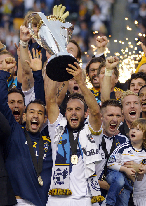 Los Angeles Galax's Landon Donovan hoist the trophy as they celebrate after defeating the Houston Dynamo 3-1 in the MLS Cup championship soccer game, Saturday, Dec. 1, 2012, in Carson, Calif. AP Photo/Mark J. Terrill)