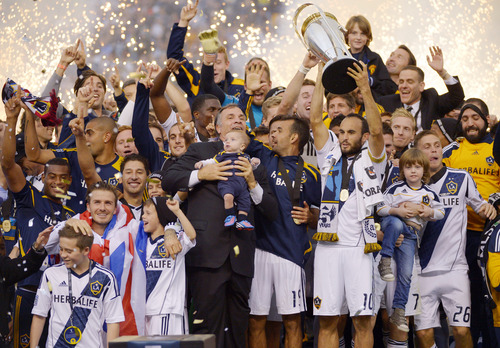 Los Angeles Galaxy, including coach Bruce Arena, center, Landon Donovan holding the trophy, and David Beckham front left, celebrate after defeating the the Houston Dynamo 3-1 in the MLS Cup championship soccer game, Saturday, Dec. 1, 2012, in Carson, Calif. AP Photo/Mark J. Terrill)