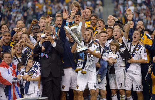 Los Angeles Galaxy, players including Landon Donovan holding the trophy, and David Beckham, front left, celebrate after defeating the the Houston Dynamo 3-1 in the MLS Cup championship soccer game, Saturday, Dec. 1, 2012, in Carson, Calif. AP Photo/Mark J. Terrill)