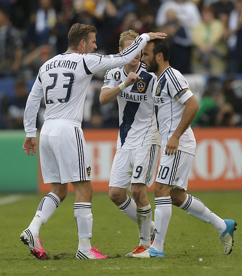 Los Angeles Galaxy's Landon Donovan, right, David Beckham, left, of England, and Christian Wilhelmsson, of Sweden, celebrate a goal by Donovan during the second half of the MLS Cup championship soccer match against the Houston Dynamo in Carson, Calif., Saturday, Dec. 1, 2012. (AP Photo/Jae C. Hong)