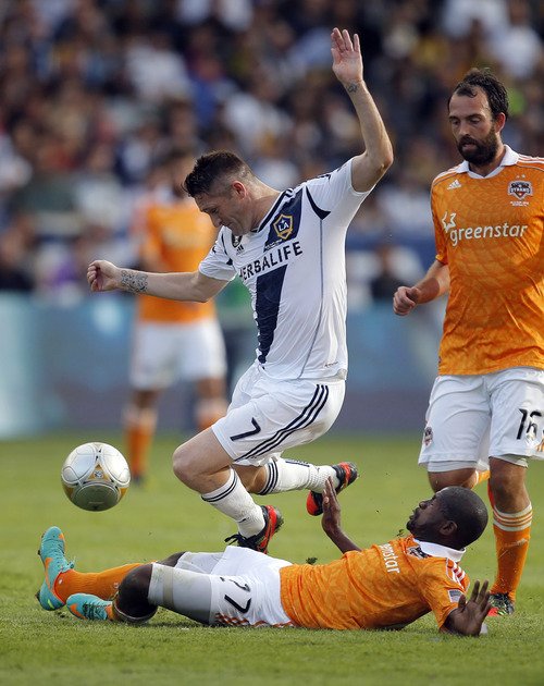 Los Angeles Galaxy's Robbie Keane, top, of Ireland, is tackled by Houston Dynamo's Boniek Garcia during the first half of the MLS Cup championship soccer match against the Houston Dynamo in Carson, Calif., Saturday, Dec. 1, 2012. (AP Photo/Jae C. Hong)