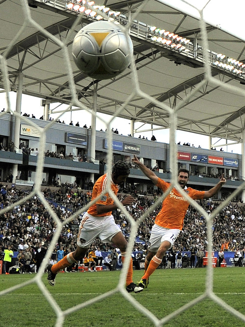 Houston Dynamo defender Kofi Sarkodie, left, and forward Will Bruin celebrate a goal by forward Calen Carr during the first half of the MLS Cup championship soccer match against the Los Angeles Galaxy in Carson, Calif., Saturday, Dec. 1, 2012. (AP Photo/Jae C. Hong)
