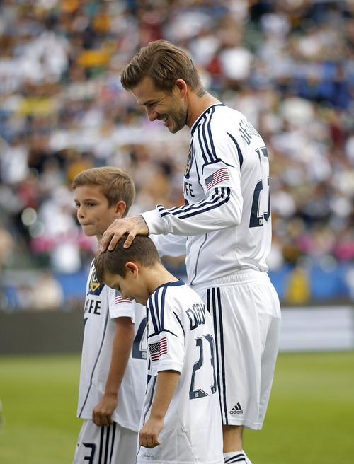 Los Angeles Galaxy's David Beckham, of England, walks with his sons, Romeo, background, left, and Cruz before the MLS Cup championship soccer match against the Houston Dynamo in Carson, Calif., Saturday, Dec. 1, 2012. (AP Photo/Jae C. Hong)