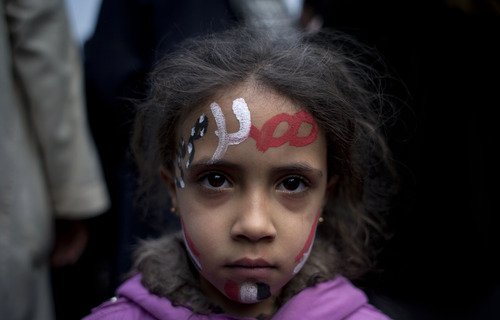 """A girl with the colors of Egypt's national flag and Arabic that reads, """"Egypt, Morsi,"""" painted on her face attends a demonstration in front of Egypt's top court, in Cairo, Egypt, Sunday, Dec. 2, 2012. Egypt's top court announced on Sunday the suspension of its work indefinitely to protest """"psychological and physical pressures,"""" saying its judges could not enter its Nile-side building because of the Islamist president's supporters gathered outside. (AP Photo/Nasser Nasser)"""