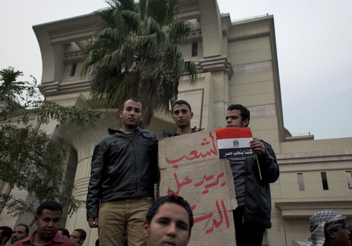 """Supporters of Egyptian President Mohammed Morsi hold a placard with Arabic that reads, """"the people want to solve the constitution,"""" outside Egypt's top court in Cairo, Sunday, Dec. 2, 2012. Egypt's top court announced on Sunday the suspension of its work indefinitely to protest """"psychological and physical pressures,"""" saying its judges could not enter its Nile-side building because of the Islamist president's supporters gathered outside. (AP Photo/Nasser Nasser)"""