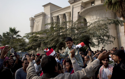 """Supporters of Egyptian President Mohammed Morsi chant slogans in front of Egypt's top court, background, in Cairo, Egypt, Sunday, Dec. 2, 2012. Egypt's top court announced on Sunday the suspension of its work indefinitely to protest """"psychological and physical pressures,"""" saying its judges could not enter its Nile-side building because of the Islamist president's supporters gathered outside. (AP Photo/Nasser Nasser)"""