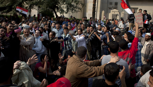 """Supporters of Egyptian President Mohammed Morsi hold national flags and dance in front of Egypt's top court, background, in Cairo, Egypt, Sunday, Dec. 2, 2012. Egypt's top court announced on Sunday the suspension of its work indefinitely to protest """"psychological and physical pressures,"""" saying its judges could not enter its Nile-side building because of the Islamist president's supporters gathered outside. (AP Photo/Nasser Nasser)"""