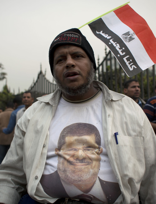 """A man wears a T-shirt with the portrait of Egyptian President Mohammed Morsi with a national flag attached to his beanie with Arabic that reads, """"we all love Egypt,"""" in front of Egypt's top court in Cairo, Egypt, Sunday, Dec. 2, 2012. Egypt's top court announced on Sunday the suspension of its work indefinitely to protest """"psychological and physical pressures,"""" saying its judges could not enter its Nile-side building because of the Islamist president's supporters gathered outside. (AP Photo/Nasser Nasser)"""