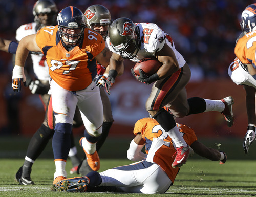 Tampa Bay Buccaneers running back Doug Martin (22) is tripped up by Denver Broncos free safety Rahim Moore (26) as Denver Broncos defensive tackle Justin Bannan (97) helps defend in the first quarter of an NFL football game, Sunday, Dec. 2, 2012, in Denver. (AP Photo/Joe Mahoney)