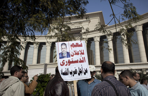 """A supporter of Egyptian President Mohammed Morsi holds a banner with his picture and Arabic that reads, """"yes for the constitutional declaration to stop corruption,"""" during a protest in front of Egypt's top court, in Cairo, Egypt, Monday, Dec. 3, 2012. The Egyptian president's top legal adviser says the country's election commission has begun preparations for the referendum on Dec. 15 on a highly contentious draft constitution. (AP Photo/Nasser Nasser)"""