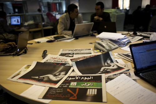 """Egyptian journalists at the editorial room of al-Masri al-Youm daily newspaper next to copies of Egypt's most prominent newspapers running black background front pages with Arabic that reads, """"no to dictatorship, tomorrow free newspapers will obscure to protest the freedom's restrictions,"""" and a picture of a man wrapped in newspapers with his feet cuffed, in Cairo, Egypt, Monday, Dec. 3, 2012. Eleven Egyptian newspapers are planning to suspend publication on Tuesday to protest against President Mohammed Morsi's decision to call a constitution referendum on 15 December. (AP Photo/Nasser Nasser)"""