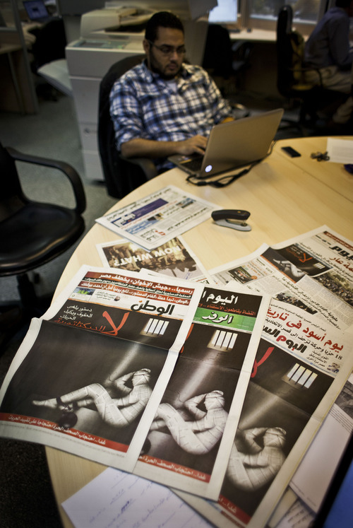"""An Egyptian journalist works at the editorial room of al-Masri al-Youm daily newspaper next to copies of Egypt's most prominent newspapers running black background front pages with Arabic that reads, """"no to dictatorship, tomorrow free newspapers will obscure to protest the freedom's restrictions,"""" and a picture of a man wrapped in newspapers with his feet cuffed, in Cairo, Egypt, Monday, Dec. 3, 2012. Eleven Egyptian newspapers are planning to suspend publication on Tuesday to protest against President Mohammed Morsi's decision to call a constitution referendum on 15 December. (AP Photo/Nasser Nasser)"""