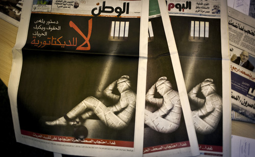 """Copies of Egypt's most prominent newspapers running black background front pages with Arabic that reads, """"no to dictatorship, tomorrow free newspapers will obscure to protest the freedom's restrictions"""" and a picture of a man wrapped in newspaper with his feet cuffed, at the editorial room of Al Masry Al Youm daily newspaper in Cairo, Egypt, Monday, Dec. 3, 2012. Eleven Egyptian newspapers are planning to suspend publication on Tuesday to protest against President Mohammed Morsi's decision to call a constitution referendum on 15 December. (AP Photo/Nasser Nasser)"""