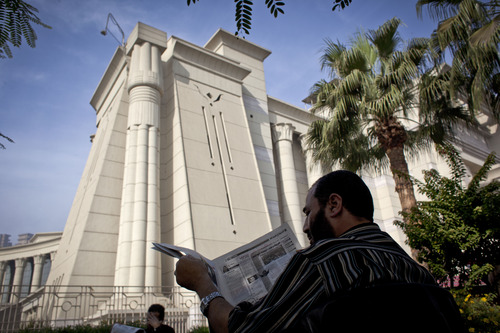 A supporter of Egyptian President Mohammed Morsi reads a newspaper during a protest in front of Egypt's top court, in Cairo, Egypt, Monday, Dec. 3, 2012. The Egyptian president's top legal adviser says the country's election commission has begun preparations for the referendum on Dec. 15 on a highly contentious draft constitution. (AP Photo/Nasser Nasser)
