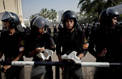 Riot policemen eat their lunch as they stand guard in front of Egypt's top court during a protest for supporters of Egyptian President Mohammed Morsi, unseen, in Cairo, Egypt, Monday, Dec. 3, 2012. The Egyptian president's top legal adviser says the country's election commission has begun preparations for the referendum on Dec. 15 on a highly contentious draft constitution. (AP Photo/Nasser Nasser)