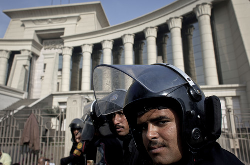 Riot policemen stand guard in front of Egypt's top court during a protest for supporters of Egyptian President Mohammed Morsi, unseen, in Cairo, Egypt, Monday, Dec. 3, 2012. The Egyptian president's top legal adviser says the country's election commission has begun preparations for the referendum on Dec. 15 on a highly contentious draft constitution. (AP Photo/Nasser Nasser)