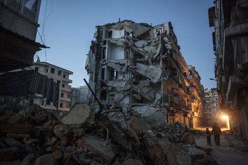 In this Sunday, Dec. 2, 2012 photo, residents walk past damaged buildings due to heavy fighting between Free Syrian Army fighters and government forces in Aleppo, Syria. (AP Photo/Narciso Contreras)