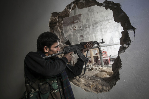 In this Sunday, Dec. 2, 2012 photo, a Free Syrian Army fighter aims his weapon during clashes with government forces in Aleppo, Syria. (AP Photo/Narciso Contreras)