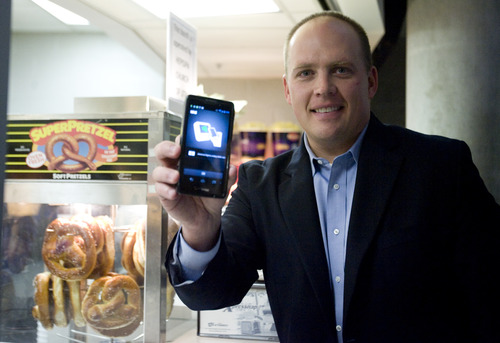 Kim Raff | The Salt Lake Tribune Dave Roberts, the local Isis City Development Manager, holds a smartphone with the Isis system that allows you to use your smartphone to pay for things.