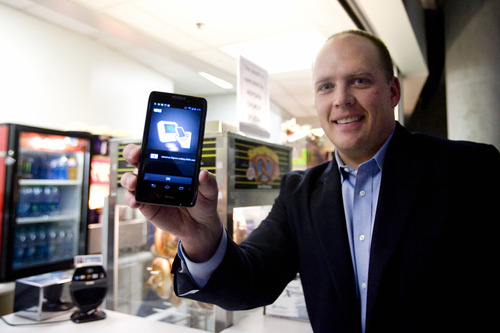 Kim Raff | The Salt Lake Tribune Dave Roberts, the local Isis City Development Manager, holds a smartphone with the Isis system that allows you to use your smartphone to pay for things at EnergySolutions Arena in Salt Lake City, Utah on November 7, 2012. The system was turned on last week in Salt Lake City and there are over a thousand retailers that use the system.