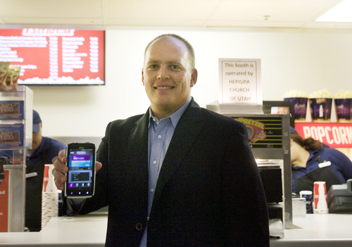 Kim Raff | The Salt Lake Tribune Dave Roberts, the local Isis City Development Manager, holds a smartphone with the Isis system that allows you to use your smartphone to pay for thing.