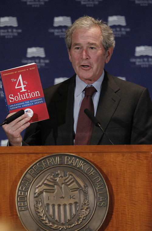 "Former President George W. Bush holds up a book as he gives opening remarks at the Federal Reserve Bank of Dallas for a conference titled ""Immigration and 4% Growth: How Immigrants grow the U.S. Economy,"" Tuesday, Dec. 4, 2012, in Dallas.  The George W. Bush Institute is hosting panel discussions highlighting the positive impact of immigration on U.S. economic growth. (AP Photo/LM Otero)"