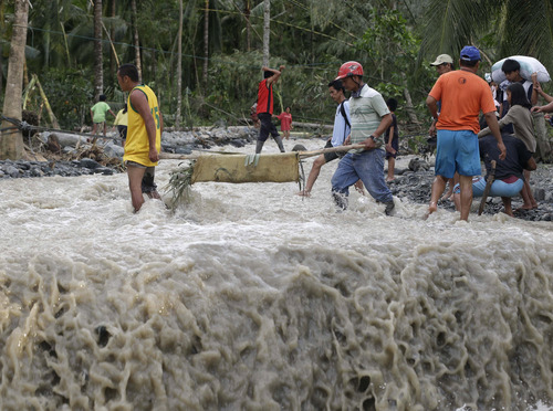 Residents cross a river with the body of a child after retrieving it from the flash flood-hit village of Andap, in New Bataan township, Compostela Valley in southern Philippines Wednesday Dec. 5, 2012, a day after the devastating Typhoon Bopha made landfall. Typhoon Bopha, one of the strongest typhoons to hit the Philippines this year, barreled across the country's south on Tuesday, killing scores of people while triggering landslides, flooding and cutting off power in two entire provinces. (AP Photo/Bullit Marquez)