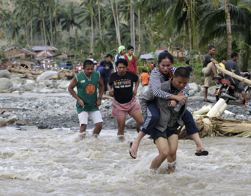Residents cross a river in the flash flood-hit village of Andap, New Bataan township, Compostela Valley in southern Philippines Wednesday, Dec. 5, 2012.  Typhoon Bopha, one of the strongest typhoons to hit the Philippines this year, barreled across the country's south on Tuesday, killing scores of people while triggering landslides, flooding and cutting off power in two entire provinces. (AP Photo/Bullit Marquez)