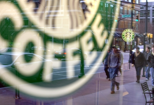 FILE - In this Wednesday, Jan. 26, 2011, file photo, pedestrians are reflected outside a Starbucks store in Atlanta. Starbucks, the world's biggest coffee company, is planning to add at least 1,500 cafes in the U.S. over the next five years. The plan, which would boost the number of Starbucks cafes in the country by about 13 percent, was announced at the company's investor day in New York,Wednesday. Taking into account Canada and South America, the company plans to add a total of 3,000 new cafes in its broader Americas region. (AP Photo/David Goldman, File)