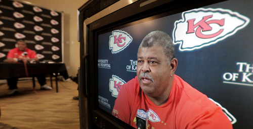 Kansas City Chiefs coach Romeno Crennel appears on a television monitor as he talks about linebacker Jovan Belcher during a news conference Monday, Dec. 3, 2012, at the NFL football team's practice facility in Kansas City, Mo. Crennel and Chiefs general manager Scott Pioli witnessed Belcher's suicide at the practice facility Saturday after, police said, Belcher shot and killed his girlfriend, Kasandra Perkins, at their Kansas City-area home. (AP Photo/Charlie Riedel)