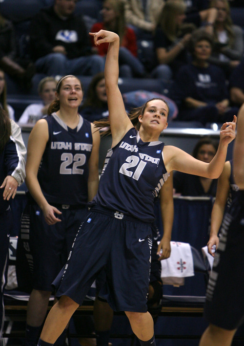 Steve Griffin   The Salt Lake Tribune   USU's Makenlee WIlliams holds her follow through as she launches a three-pointer during game against BYU at the Marriott Center in Provo, Utah Tuesday December 4, 2012.