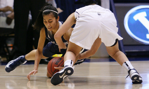 Steve Griffin   The Salt Lake Tribune   USU's Jennifer Schlott dives for the ball as BYU's Kylie Maeda treis to scoop it up during game at the Marriott Center in Provo, Utah Tuesday December 4, 2012.