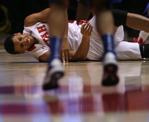 Steve Griffin | The Salt Lake Tribune   Utah's jordan Loveridge grimaces after his leg got pinned under a Boise State player during first-half play at the Huntsman Center  in Salt Lake City on Wednesday, Dec. 5, 2012.