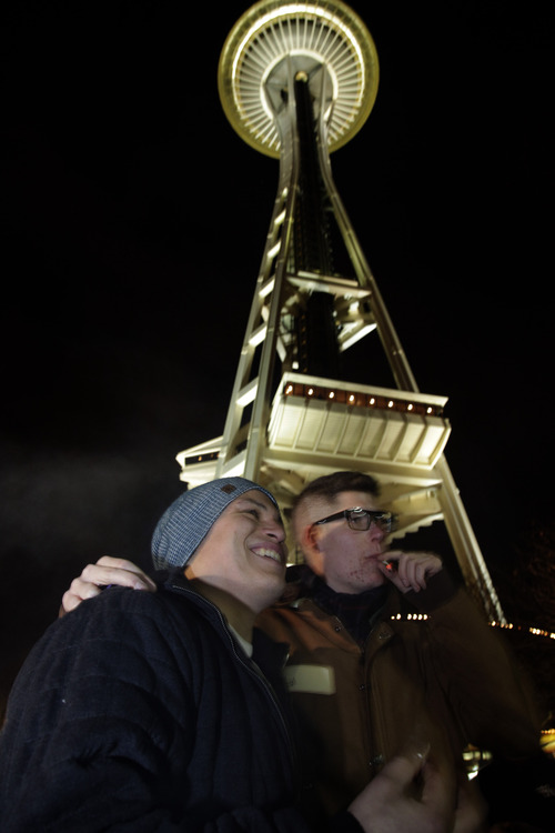 David DesRoaches, left, and Michael Hodges, right, pose for a friend's photo as they smoke marijuana, Thursday, Dec. 6, 2012, just after midnight at the Space Needle in Seattle. Possession of marijuana became legal in Washington state at midnight, and several hundred people gathered at the Space Needle to smoke and celebrate the occasion, even though the new law does prohibit public use of marijuana. (AP Photo/Ted S. Warren)