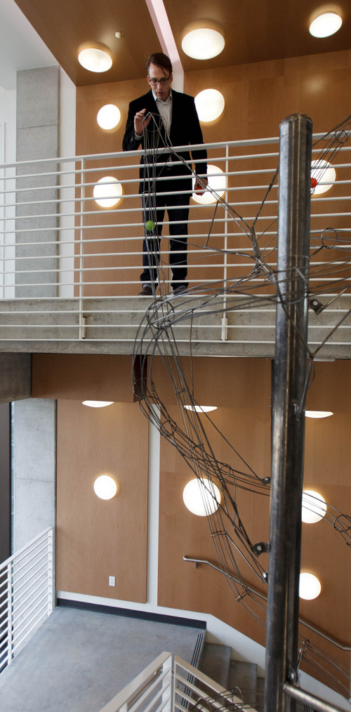 Trent Nelson  |  The Salt Lake Tribune Brad Rencher, senior vice president and general manager, drops a plastic ball into a piece of art that goes the length of a four-story staircase at the new Adobe building Thursday December 6, 2012 in Lehi.
