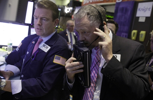 FILE - In this Thursday, Dec. 6, 2012, file photo, specialist Michael O'mara, left, and trader Robert Moran work on the floor of the New York Stock Exchange, in New York. Stock markets were in a holding pattern ahead of a U.S. jobs report later Friday Dec. 7, 2012 that is expected to reflect a downturn in hiring following a massive storm but could also show that the American economy is otherwise bouncing back.  (AP Photo/Richard Drew, File)