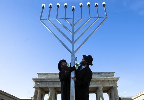 Rabbi Yehuda Teichtal, right, and Rabbi Segal Shmoel, left, install a giant Hanukkah Menorah, at the Pariser Platz in front of the Brandeburg Gate in Berlin, Friday, Dec. 7, 2012. The eight day Jewish Festival of Lights, Hanukkah will start on Dec. 8. (AP Photo/Markus Schreiber)