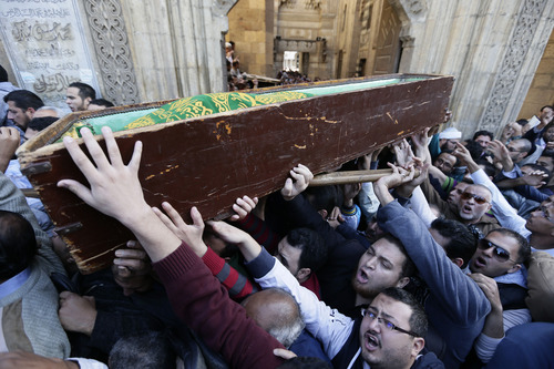 """Muslim Brotherhood and Egyptian President Morsi supporters carry a body of one of the six victims who were killed during Wednesday's clashes during their funeral outside Al Azhar mosque, the highest Islamic Sunni institution, Friday, Dec. 7, 2012. During the funeral, thousands Islamist mourners chanted, """"with blood and soul, we redeem Islam,"""" pumping their fists in the air. """"Egypt is Islamic, it will not be secular, it will not be liberal,"""" they chanted as they walked in a funeral procession that filled streets around Al-Azhar mosque. Thousands of Egyptians took to the streets after Friday midday prayers in rival rallies and marches across Cairo, as the standoff deepened over what opponents call the Islamist president's power grab, raising the specter of more violence. (AP Photo/Hassan Ammar)"""