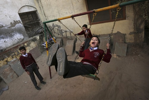 Young Indian students play on a swing after morning assembly at the Central Baptist Church School in New Delhi, India, Friday, Dec. 7, 2012. Built in 1814, the church is one of Delhi's oldest and stands on the historic Chadni Chowk Road. (AP Photo/Kevin Frayer)