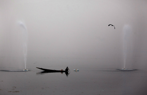 A Kashmiri fisherman rows past water fountains on a cold and foggy day at the Dal Lake in Srinagar, India, Friday, Dec. 7, 2012. The Dal Lake, which is one of the major tourist attractions of the valley, has numerous floating gardens that produce different varieties of vegetables during all four seasons of the year.(AP Photo/ Dar Yasin)