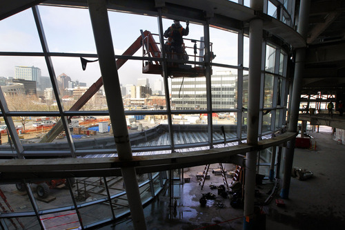 Al Hartmann  |  The Salt Lake Tribune A worker on a high lift works on the north side exterior windows of the new Salt Lake City Public Safety Building at the corner of 300 East and 500 South with its view of downtown Salt Lake to the northwest on Thursday, Dec. 6, 2012. Below is the main atrium lobby. The building is about 75 percent complete. The sweeping lines of the building with hundreds of windows complements the design of the Salt Lake Public Library to the west.