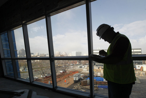 Al Hartmann  |  The Salt Lake Tribune A worker looks over plans on the inside the new Salt Lake City Public Safety Building at the corner of 300 East and 500 South with its view of downtown Salt Lake to the northwest on Thursday, Dec. 6, 2012. The building is about 75 percent complete.