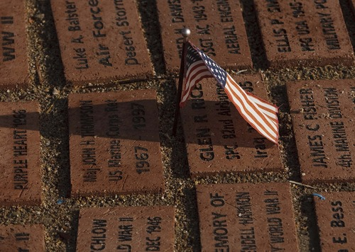 Leah Hogsten  |  The Salt Lake Tribune A small American flag pokes through the ground between pavers placed in remembrance of war veterans at the George E. Wahlen Veterans Home on Friday in Ogden. The Budweiser Clydesdale team visited veterans and their families at the home on Friday, where the Utah Department of Veterans Affairs held a Pearl Harbor remembrance ceremony.