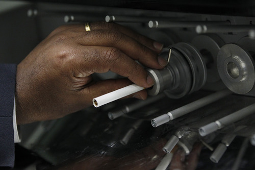 In this Thursday, April 19, 2012 photo, a cigarette is positioned in a mainstream linear 20-port smoking machine at the U.S. Department of Treasury's Alcohol and Tobacco Tax and Trade Bureau laboratory, in Beltsville, Md. The Alcohol and Tobacco Tax and Trade Bureau, which collects taxes on booze and smokes and tells the companies that produce them how to do business, is one example of the specialized government offices threatened by Washington's current zeal for cost-cutting. (AP Photo/Charles Dharapak)