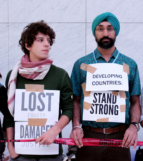 """Local and international activists protest inside a conference center to demand urgent action to address climate change at the U.N. climate talks in Doha, Qatar, Saturday, Dec. 8, 2012. After all-night wrangling, the latest draft agreements Saturday lacked the strong commitments on climate action and financing by rich countries that poor countries had hoped for. But they did include a text on """"loss and damage,"""" a relatively new concept which relates to damages from climate-related disasters. (AP Photo/Osama Faisal)"""